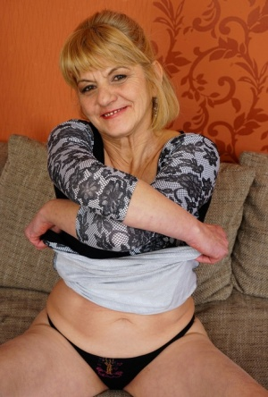 Mature lady hikes up her dress to expose up skirt underwear on her sofa 94677127