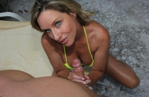 Middle-aged blonde Jodi West jerks off a cock with natural tits free of bikini