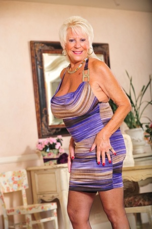 Mature blonde woman Mandi McGraw uncorks her huge boobs as she disrobes