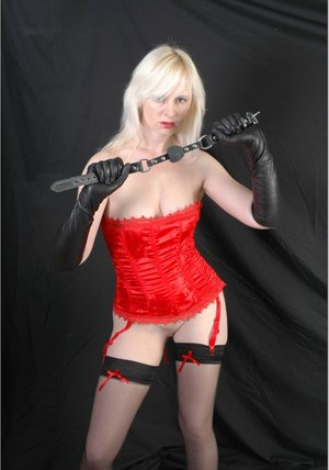Platinum blonde holds a gag with leather gloves after rubbing it over her cunt