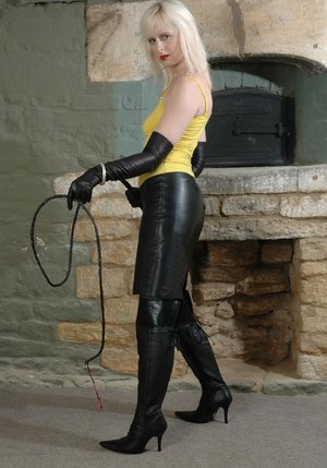 Blonde woman wields a bullwhip in a leather skirt gloves and boots