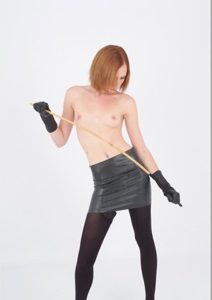 Natural redhead goes topless in a leather skirt and gloves with black hose