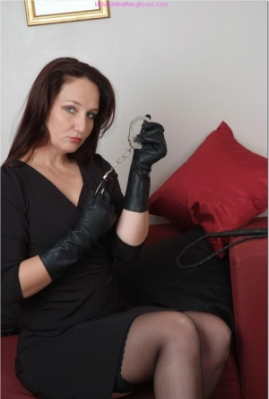 Clothed lady with long hair flashes garters and thigh in leather gloves