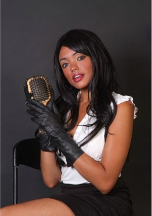 Hot black woman wields a hairbrush in black leather gloves and a skirt