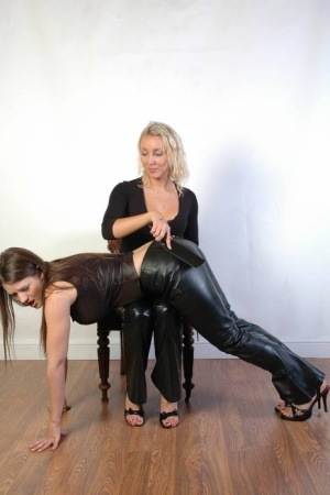 Blonde chick paddles her lesbian lovers ass while they wear leather pants
