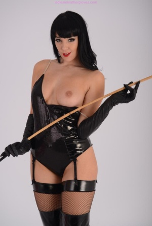 Hot brunette Sammi Jo exposes a breast while holding a cane in fetish wear