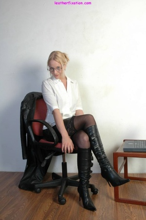 Blonde secretary flashes some thigh in black boots and a leather skirt