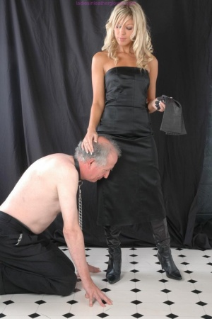 Fully clothed blonde straddles a male slave in leather boots and long gloves