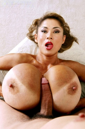 Asian cougar Minka licks a long dick before taking it between her giant tits