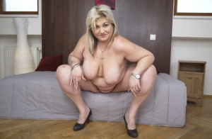 Older fatty undresses before pulling out her glass dildo