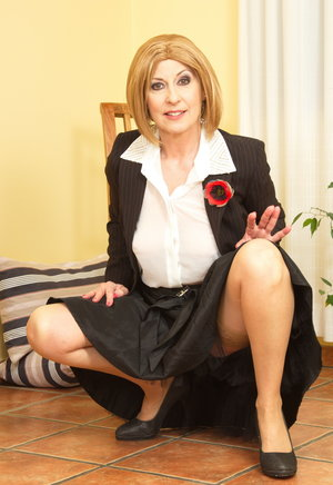 Classy mature lady sucks on a sex toy after removing business attire
