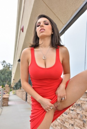 Sultry brunette chick in red dress revealing nice melons outdoors