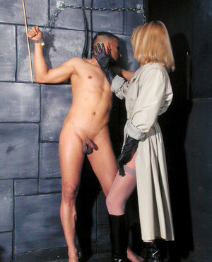 Hot blonde torments a restrained male slave in black gloves and shades