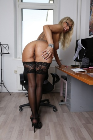 Mature blonde from Germany strips to glasses and stockings in her home office