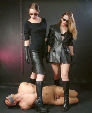 Clothed women trample a hogtied male slave with leather boots
