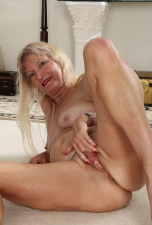 Hot granny Lis Cognee peels her dress to spread her naked mature pussy wide
