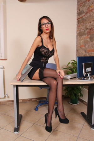 Skinny secretary with long legs frees her stocking clad feet from black pumps