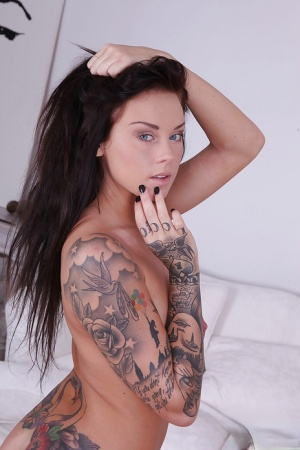 Busty tattooed hottie with pierced nipple getting rid of her clothes