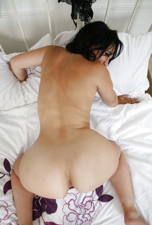 Mature babe with brunette hair Louise Bassett reveals her shaved pussy