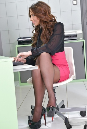 Sexy secretary in pantyhose and skirt gets naked in her office