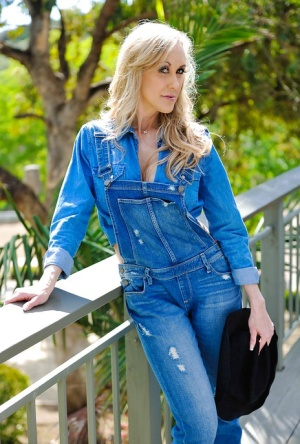 Busty MILF over 40 Brandi Love posing in cowgirl boots with gun outdoors