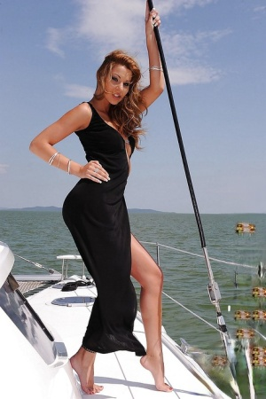 Busty pornstar Cindy Hope strips off her dress and poses on a boat