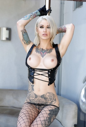 Inked blonde pornstar Kleio Valentien posing against stripper pole
