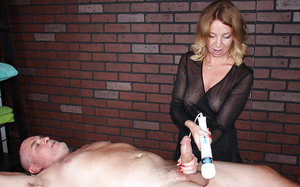 Fully clothed older blonde woman using magic wand vibrator to jack dick