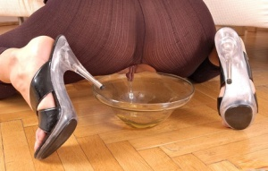 Hot chick Sandy pisses into a glass dish wearing a crotchless bodystocking