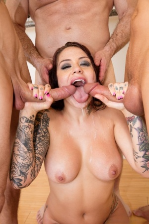 Tattooed slut Karmen Karma works up a sweat while sucking three cocks at once