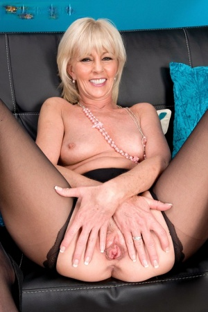 Mature blonde lady Eve Bannon spreads her long legs to finger her wet pussy
