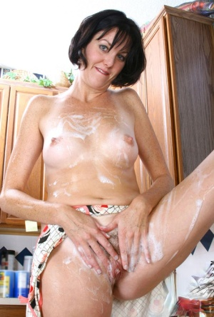 Middle aged housewife removes her apron and wets her bush in the sink