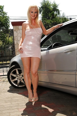 Big busted mature blonde on high heels stripping off her clothes