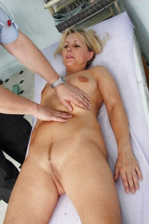 Mature blonde with puffy nipples toying her twat in gyno room 49564065