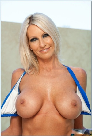 Sexy MILF Emma Starr strips booming hooters and ass from blue bikini