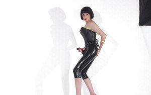 Raven-haired mature fetish lady poses in latex outfit wearing a strapon