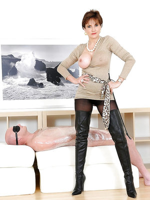 Mature femdom in high-heeled boots has some fun with her blindfolded slave