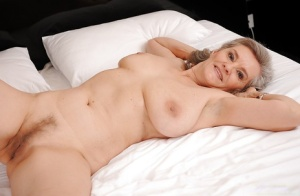 Liberated granny with massive jugs and hairy cooter stripping on the bed 87549807