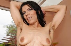 Mature lassie with saggy tits revealing her unshaven armpits and hairy twat